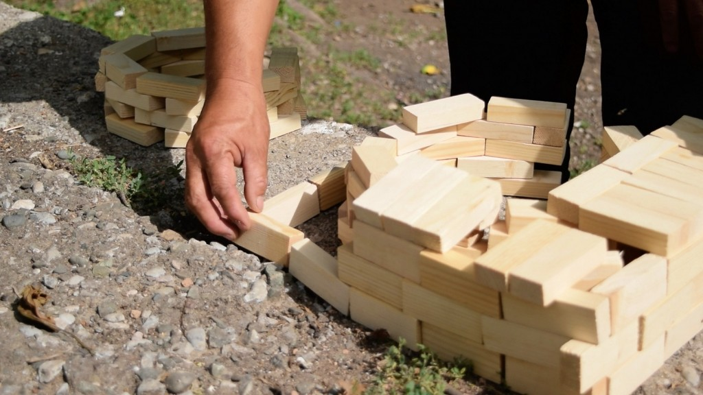 Kyrgyz master craftsman demonstrates the design of a stove using wooden blocks